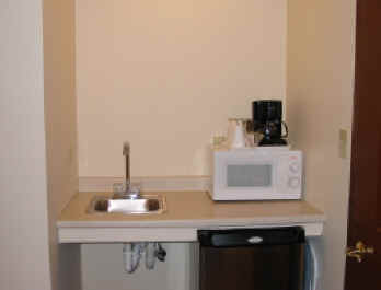 Genial Kitchenette Comes With A Microwave, Coffee Pot, Refrigerator And Sink.